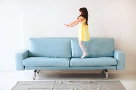 Little caucasian cute lovely girl in yellow dress playing and jumping on blue sofa in living room at home isolated on white concrete wall background. Childhood and leisure time concept