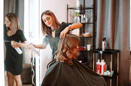 Young female hairdresser fixing hair of gorgeous smiling woman with hairspray. Hairdress and beauty concept