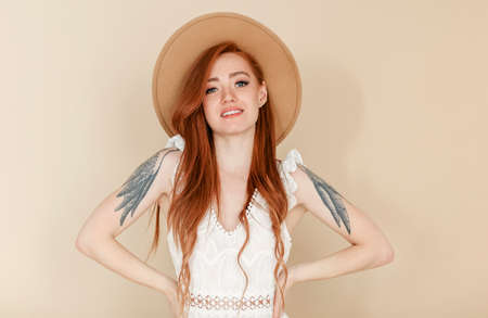 Happy redhead female with long hair and in stylish hat smiling and looking at camera Фото со стока