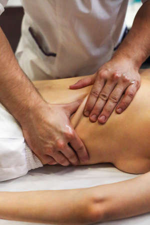 Anonymous masseuse massaging back of crop female client lying on table during procedure in spa center Фото со стока