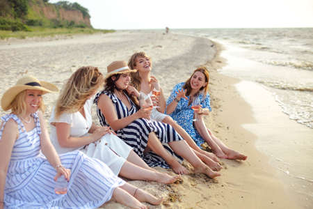 Group of delighted female friends enjoying wine and talking with each other while relaxing on sandy beach near waving sea in summer