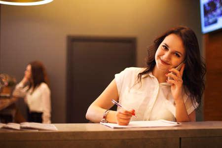 Brunette woman receptionist working in Reception of the beauty salon