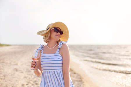 Glad adult female in summer outfit smiling and looking away while enjoying wine on sandy beach near sea Фото со стока