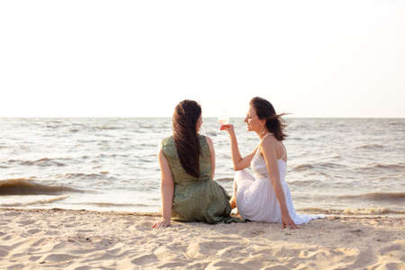 Glad adult female friends in summer outfit smiling while enjoying wine on sandy beach near sea
