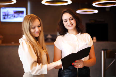 Young female receptionist working in beauty salon and writing down appointment of anonymous female customer