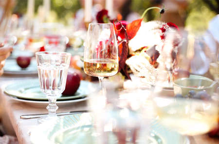 Soft focus of fresh flowers and burning candles placed amidst tableware on banquet table during event