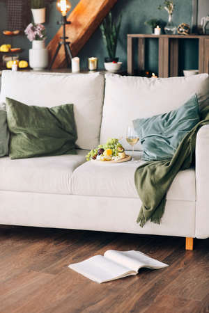Plate with fresh fruits and glass of wine placed near pillows on comfortable couch in stylish room at home