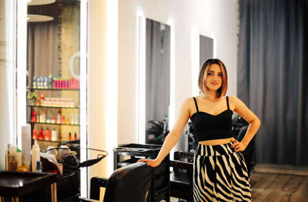 Woman working in hairdressing salon. Portrait of a young and pretty hairdresser. Hair care concept and beauty