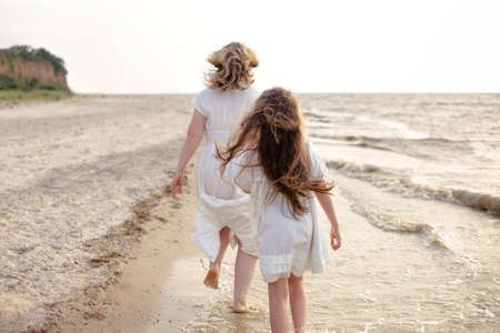 Full body cheerful woman in white dress with little girl running on beach near waving sea in morning