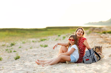 Loving mother with adorable girl in sunglasses sitting together on shore in summer at sunset Фото со стока