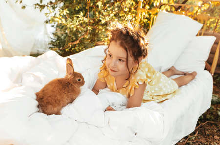 Little pretty girl in summer dress sitting outside on the bed with rabbits, cute kid looking at bunnies with light smile enjoying spending time with her favorite pets Фото со стока