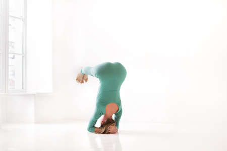 Full body of focused slim female female performing handstand near wall while practicing yoga in light room Фото со стока