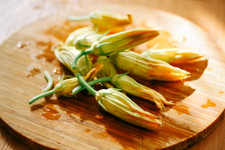 Fresh zucchini flowers on a old wooden table in sunlight Фото со стока