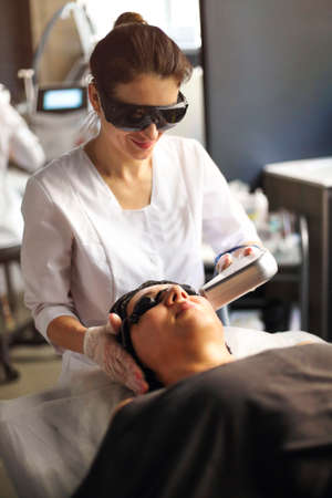 From above of female client lying on couch in beauty salon during laser epilation of her face Фото со стока