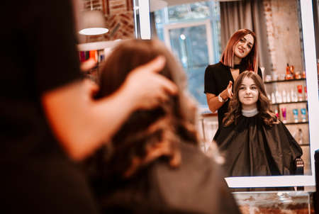 Young beautiful long haired woman smiling to the mirror to her hairstylist. Beauty service, lifestyle concep