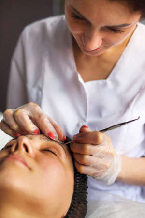 Professional beautician cleansing of acne of woman during anti aging procedure in beauty clinic