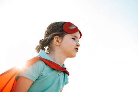 Portrait of Superhero kid against blue sky background. Joy and childhood concept