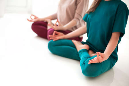 Close view of unrecognizable women in sportswear sitting with crossed legs and mudra hands on mat and doing yoga while practicing mindfulness
