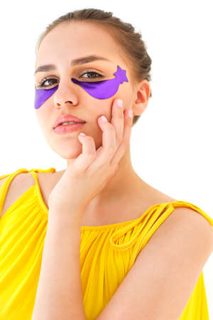 Positive young female with eye patches touching her face and looking at camera with smile during skin care routine