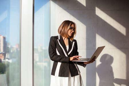 Low angle of stylish female entrepreneur with netbook adjusting glasses with smile in sunlit workspace