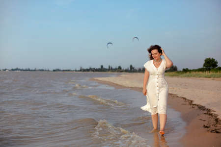 Full body adult barefoot female in white dress touching hair and walking near sea waves while spending time on sandy beach in summer Фото со стока