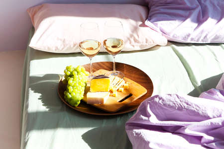 Glasses of red wine and plate with assorted food placed on comfortable bed during romantic date