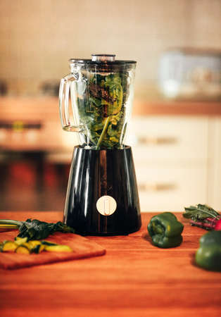 Close up photo of green vegetable smoothie blender machine in kitchen with kale leaves inside ready for grinding process. Concept of healthy diet, detoxification, healthy lifestyle, vegetarianism Фото со стока