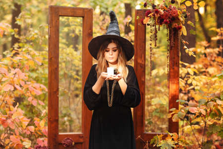 Young woman in Witch costume and hat looking mysteriously at candle in her hands isolated against autumn forest background with vintage wooden doors used as staged decoration for Halloween photo shoot Stock fotó