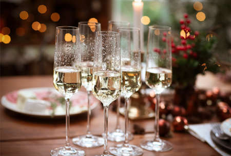 Set of champagne glasses on wooden table with candles against blurred wall with Christmas tree