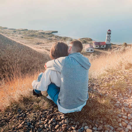 Romantic couple dressed in cozy sweaters together near the lighthouse on the sunset
