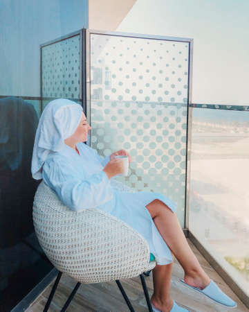 Side view of young woman in white bathrobe and towel on head sitting on armchair with cup of coffee on balcony