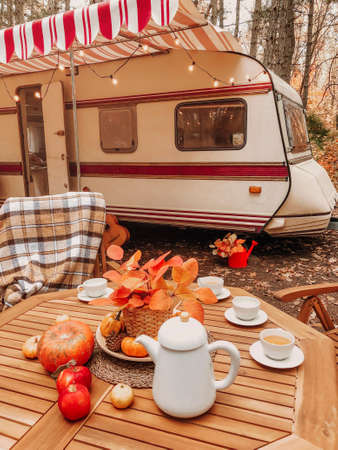 Wooden chairs and table with tea set placed outside cozy retro caravan on autumn day in peaceful countryside Stockfoto