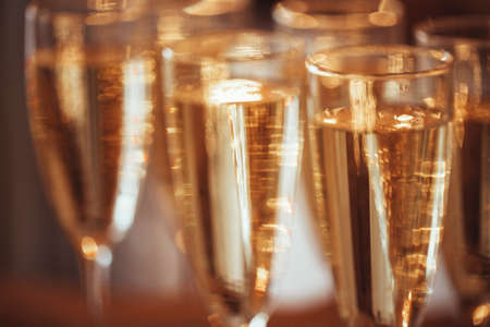 Transparent wineglasses with champagne placed on blurred background of bright illumination during party. Blured background
