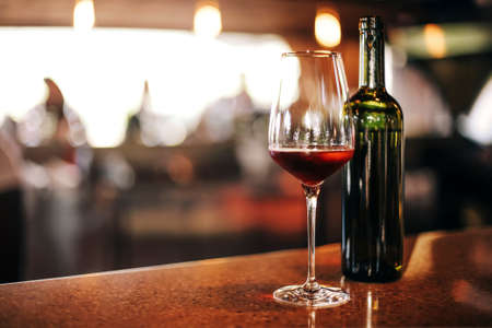Wine bottle and glasses on the table, against the background of wine dinner. Serve wine. Winemaking concept, copy space