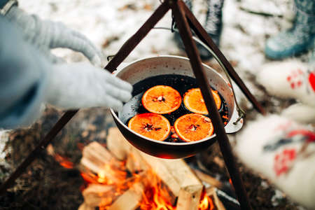 From above traditional mulled wine with slices of orange preparing in pot over burning logs in winter in countryside