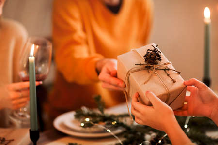 Soft focus of unrecognizable person giving wrapped gift to friend while sitting at table and celebrating Christmas together Stockfoto