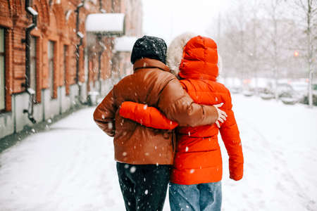 Back view of anonymous women in outerwear hugging each other and walking on snowy city street on winter day