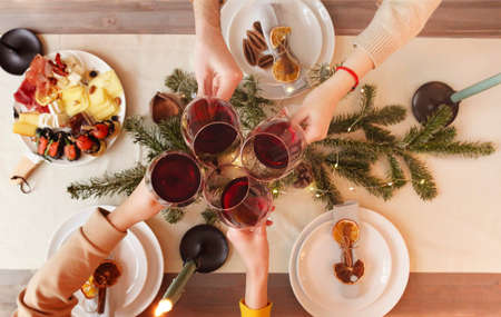 Top view of anonymous friends clinking glasses of wine over table decorated for Christmas celebration at home