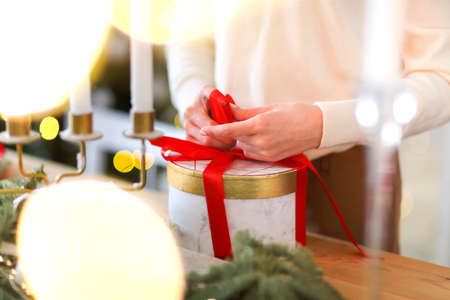 Unrecognizable lady in white sweater packing round present box tied with bright red ribbon during holiday celebration