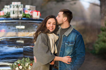 Loving man and woman by the retro car with Christmas gifts on roof in park