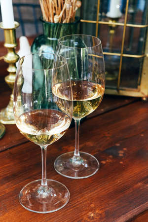 White wine in two glasses over vintage cozy bzckground. Close up