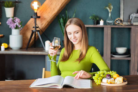 Young woman reading an interesting magazine at wooden table with fruits and wine on a weekend at home