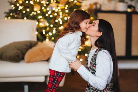 Beautiful loving mother gently kissing cute little daughter against festively decorated Christmas tree with glowing lights on background, happy family spending New Year eve at home together Stockfoto