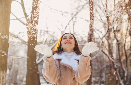 Optimistic young woman smiling while having fun on street on sunny winter day