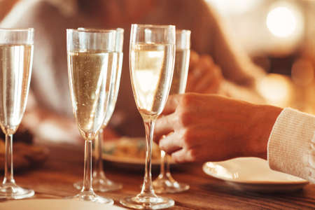 Unrecognizable female taking wineglass with champagne while standing near banquet table with burning candles during Christmas party at home