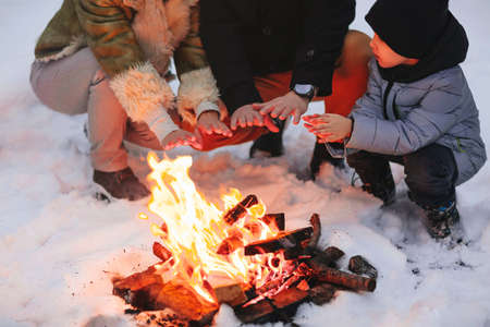 Happy family of three, mother, father and son, in warm clothes, sitting close to each other and trying to warm up by fire outside in cold snowy winter weather, against snowbound forest background