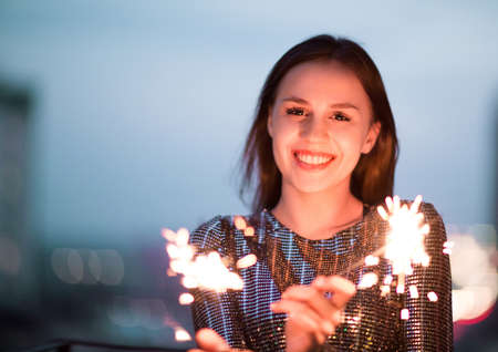 Delighted young lady in evening dress smiling and waving burning sparklers during holiday celebration at night