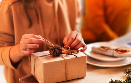Crop woman in casual outfit with Christmas gift box while sitting by the table decorated with light garland
