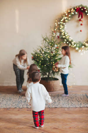 Happy four little siblings, three sisters and small brother in warm knitted sweaters gathered around fir-tree in living room and decorating it with toys and glossy balls. Family and christmas concept
