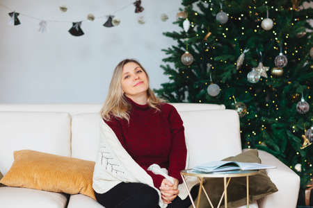 Happy caucasian joyful 50s woman sitting covered with warm knitted blanket on white cozy sofa on cushions with open book in her hands in modern living room decorated with sparking christmas fir-tree
